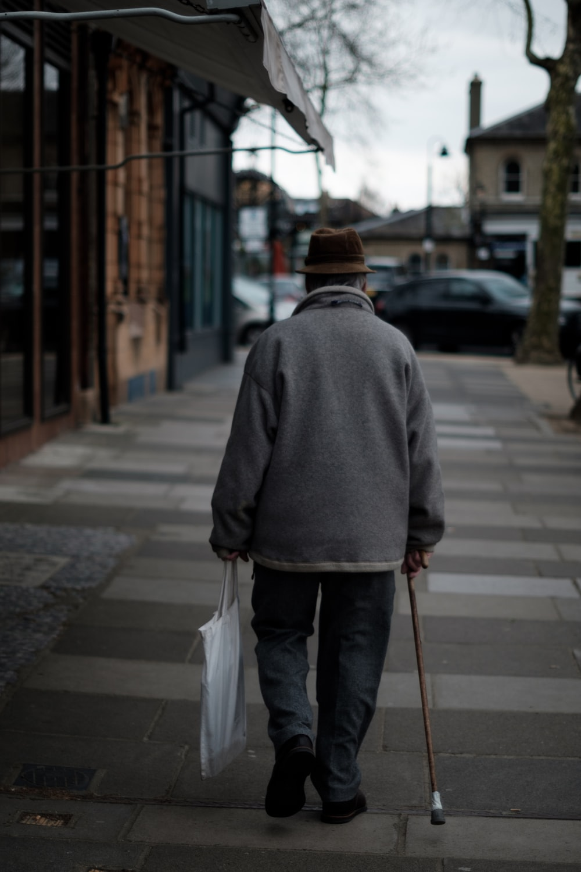man walking using brown cane carrying white bag near brown buildings at daytime