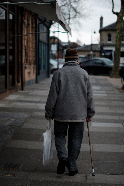 Man Walking Using Brown Cane Carrying White Bag Near Brown Buildings At Daytime Photo Free Human Image On Unsplash