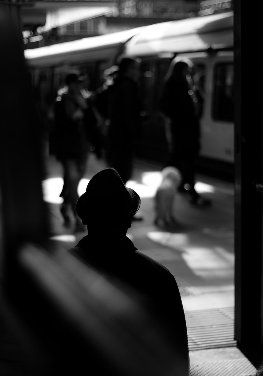 grayscale photo of person standing on train station