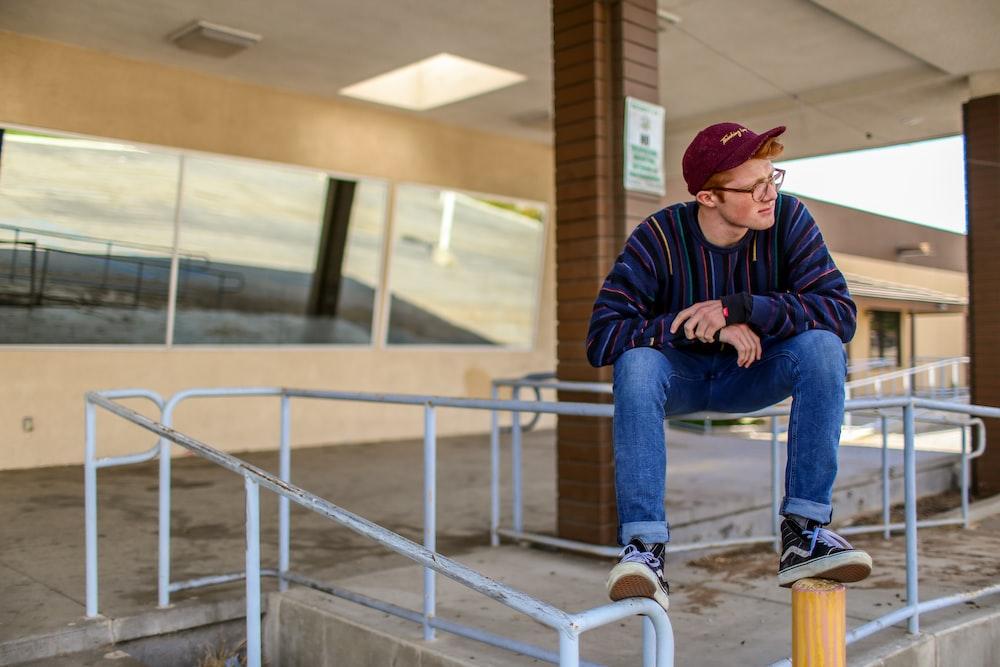 man sitting on railings