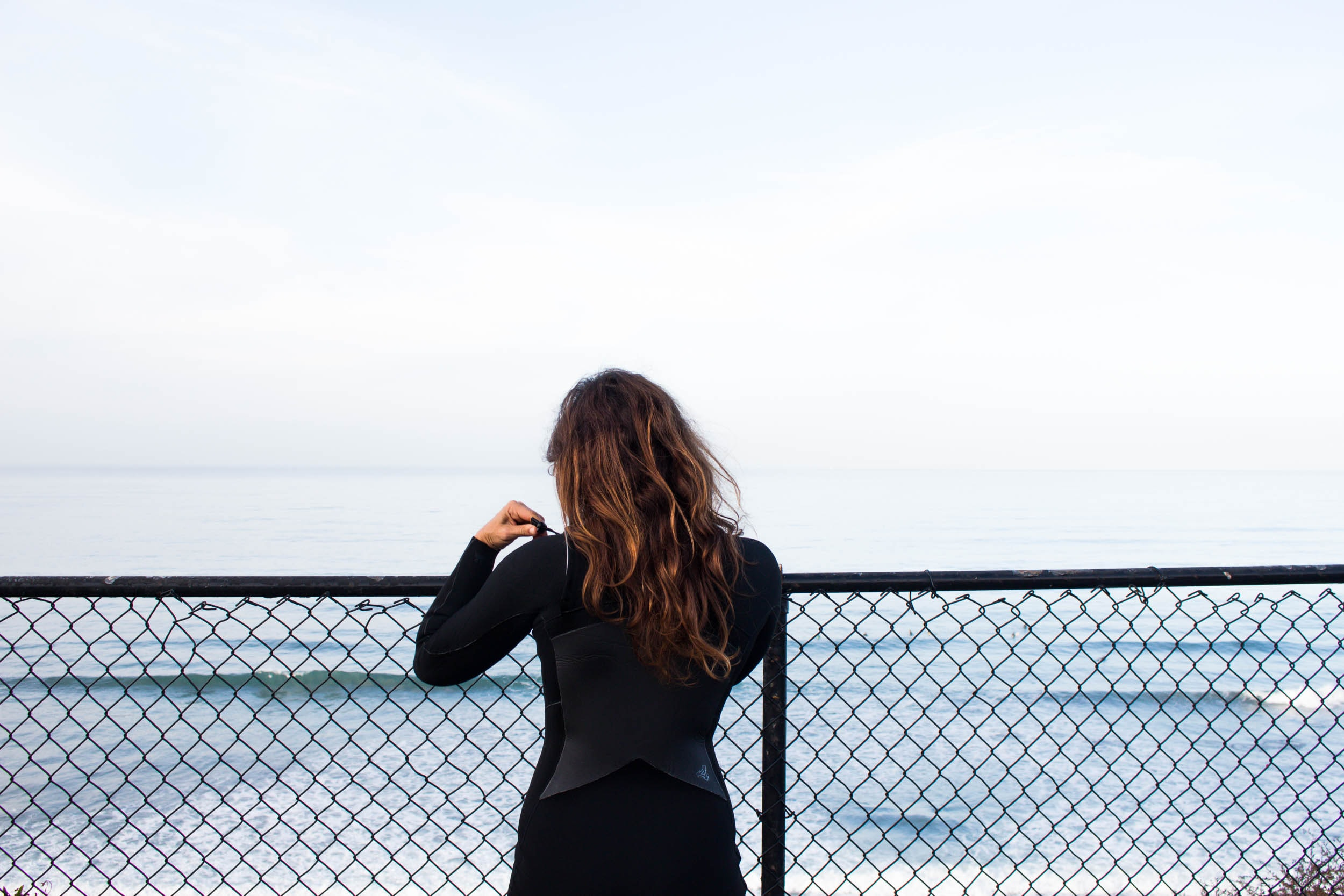woman leaning on fence facing sea