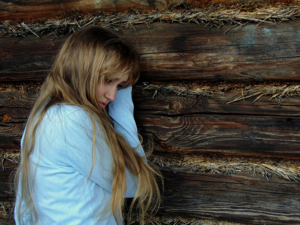 woman leaning on black wooden wall