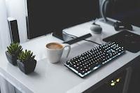 photo of turned on black gaming keyboard beside mug