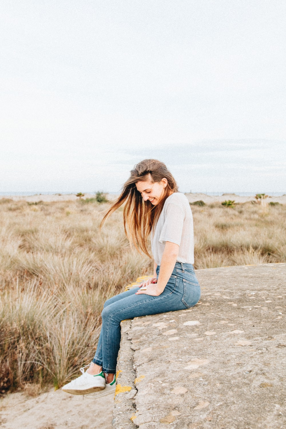 laughing woman sitting on concrete surrounded by brown grass