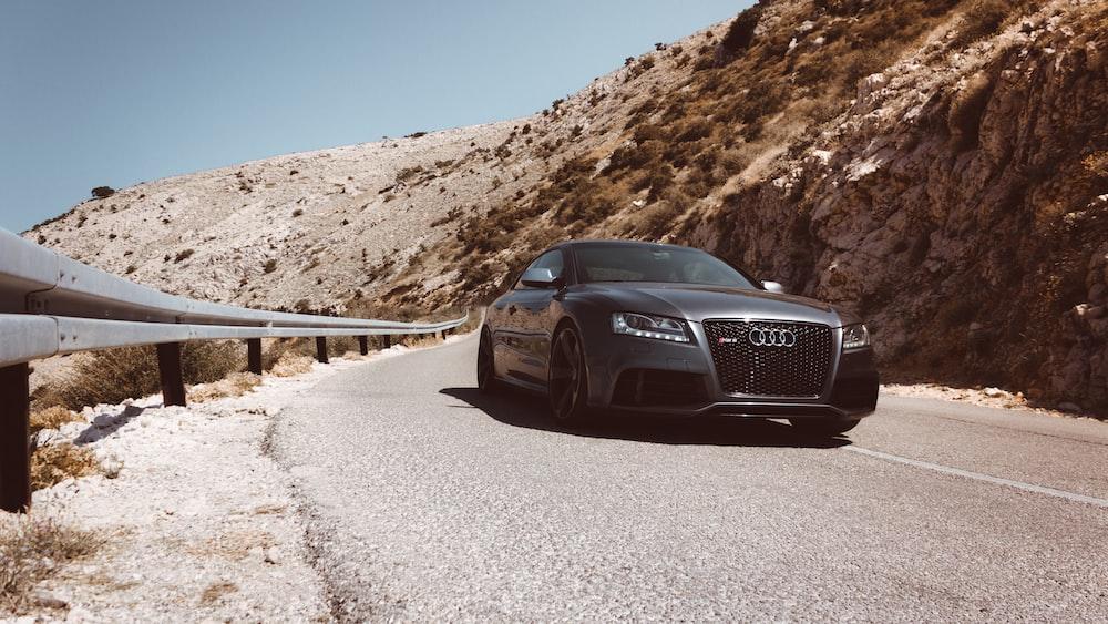 black Audi car passes on asphalt road