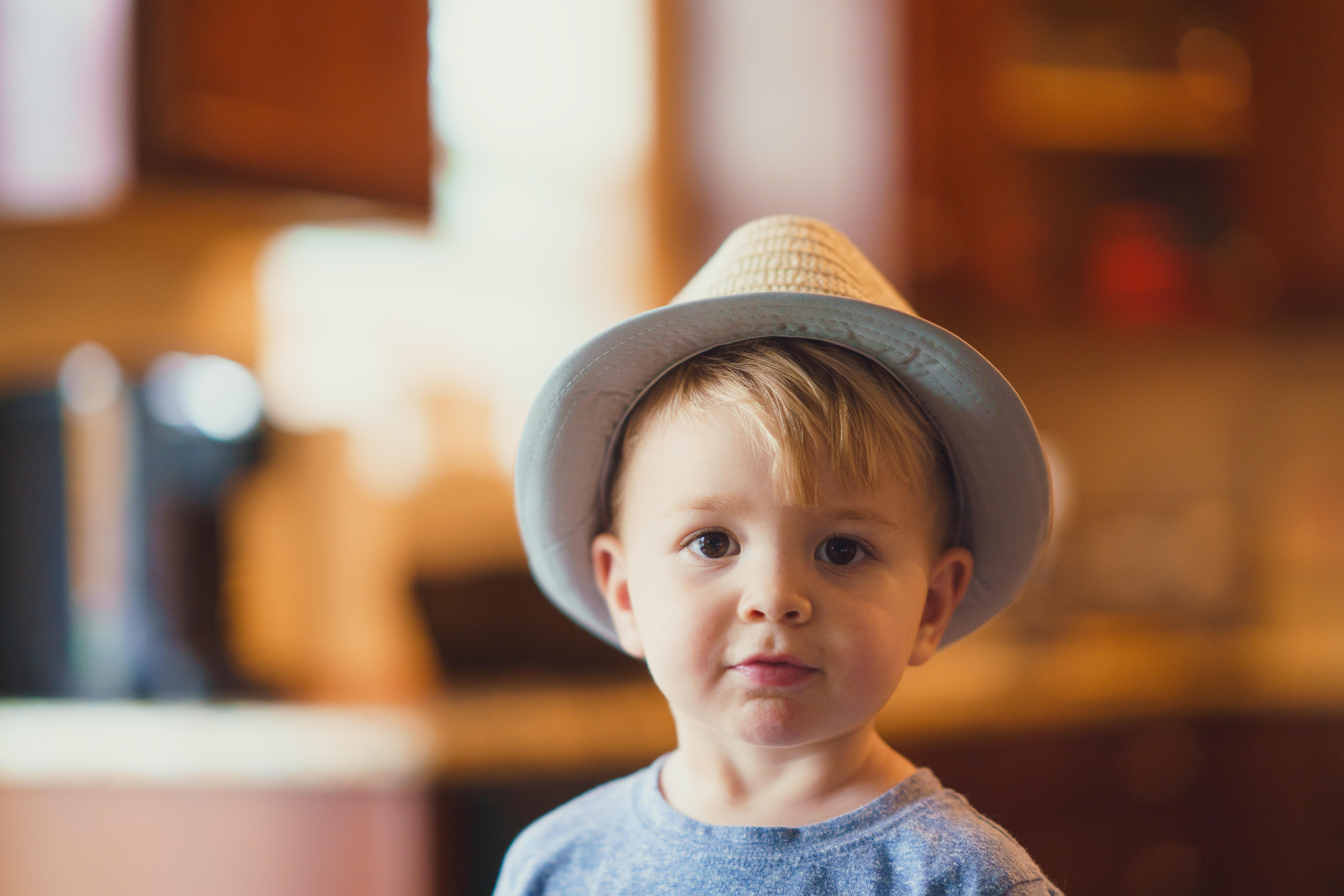 closeup photo of boy wearing brown fedora hat