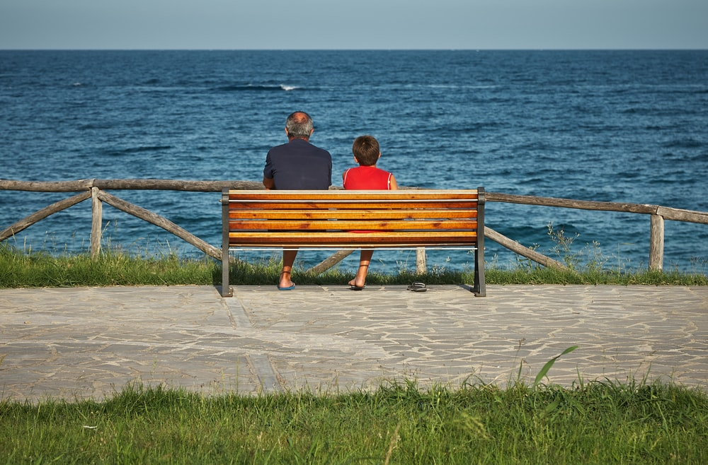 two person sitting on bench beside body of water