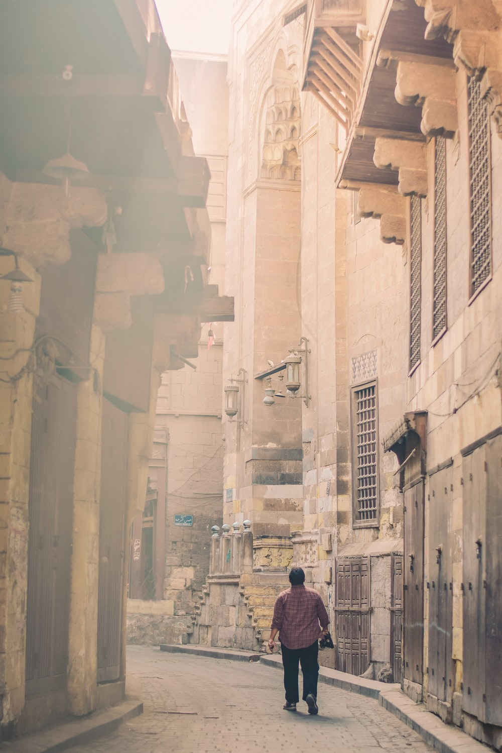 man walking between concrete buildings at daytime