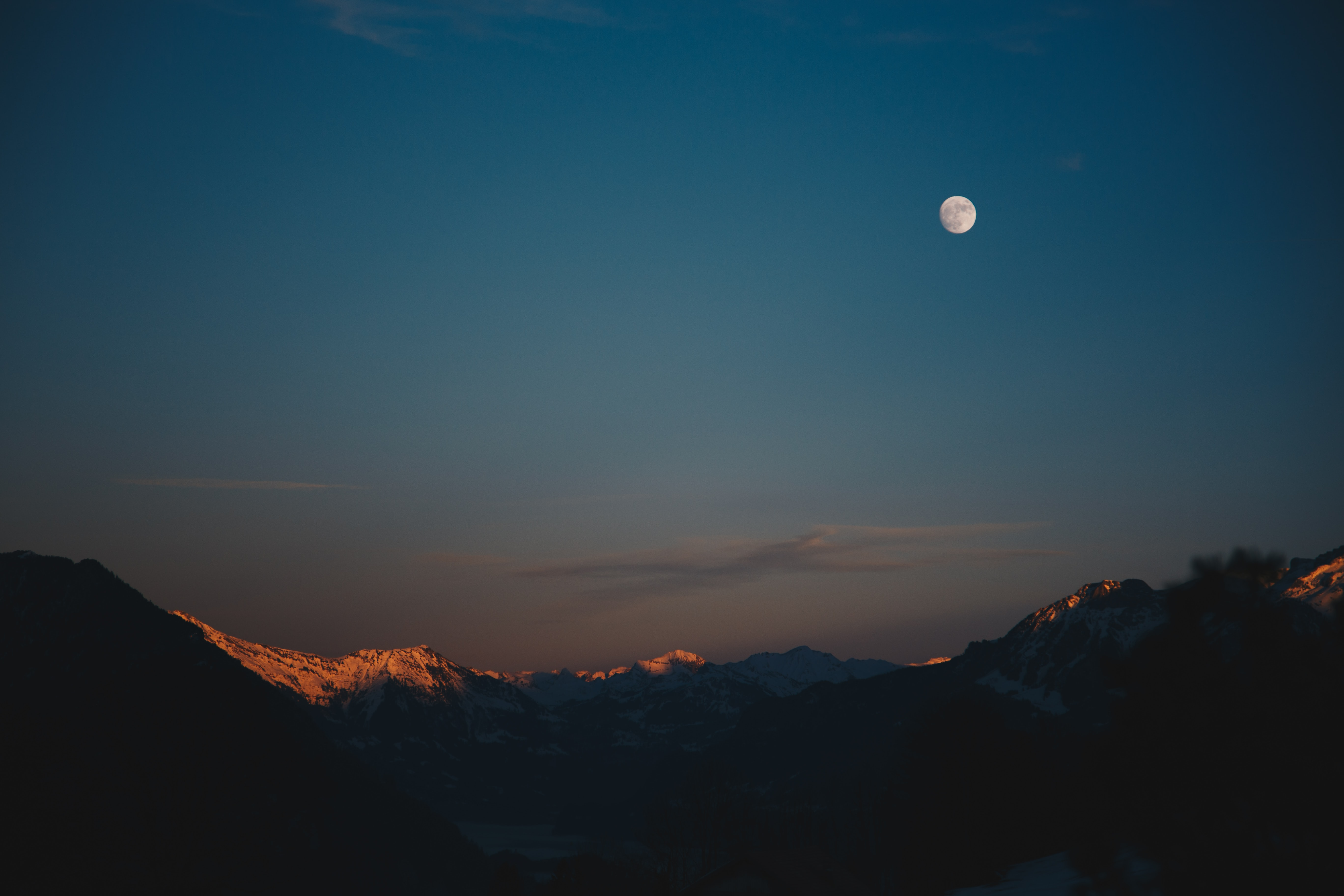 snow-capped mountain at night time with moon