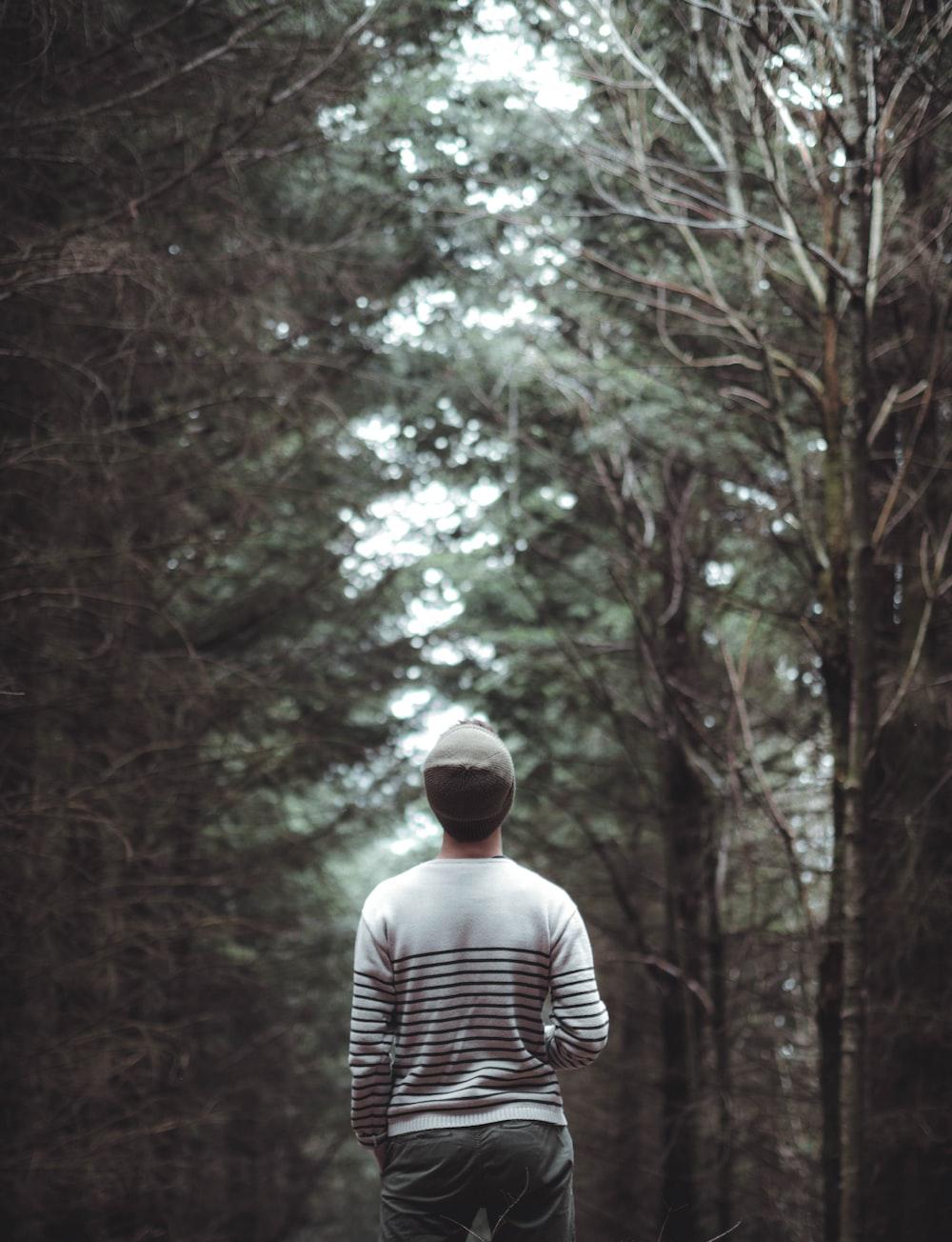 man standing between trees during daytime