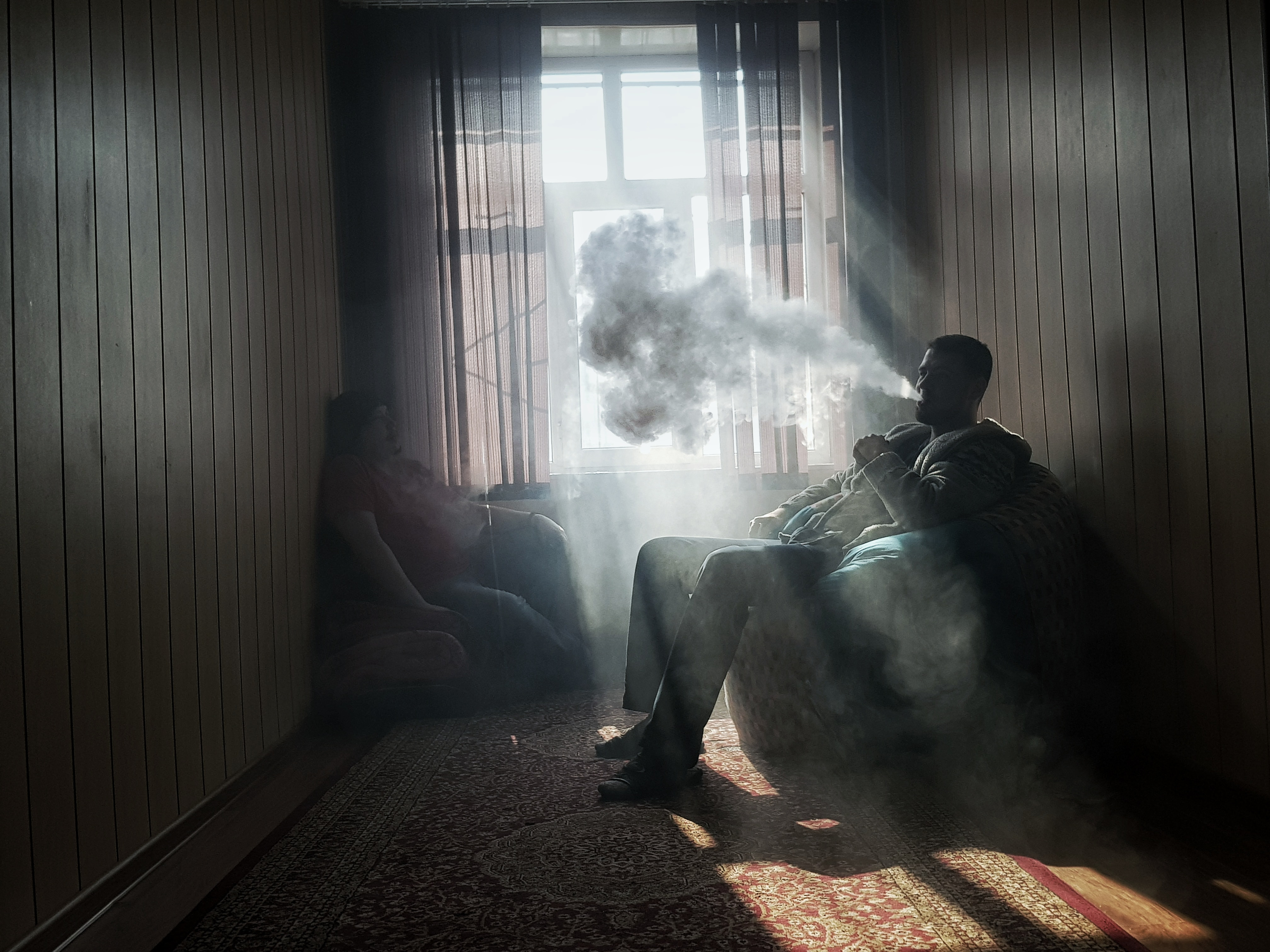 man sitting on armchair near window while smoking
