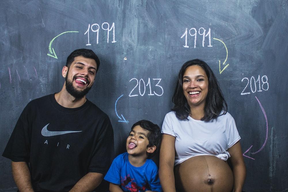 man, boy, and girl standing under chalkboard
