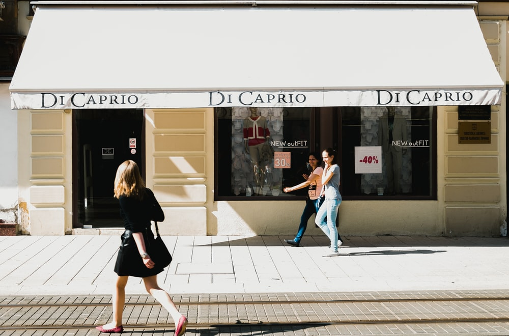 three women walking in front of Di Cario store facade