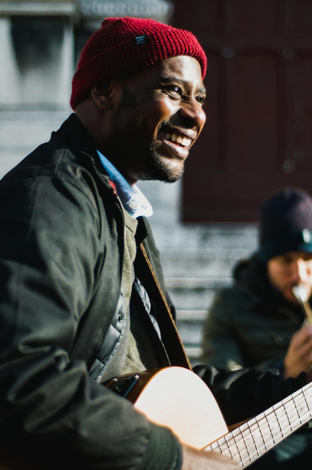 man holding guitar near man playing flute