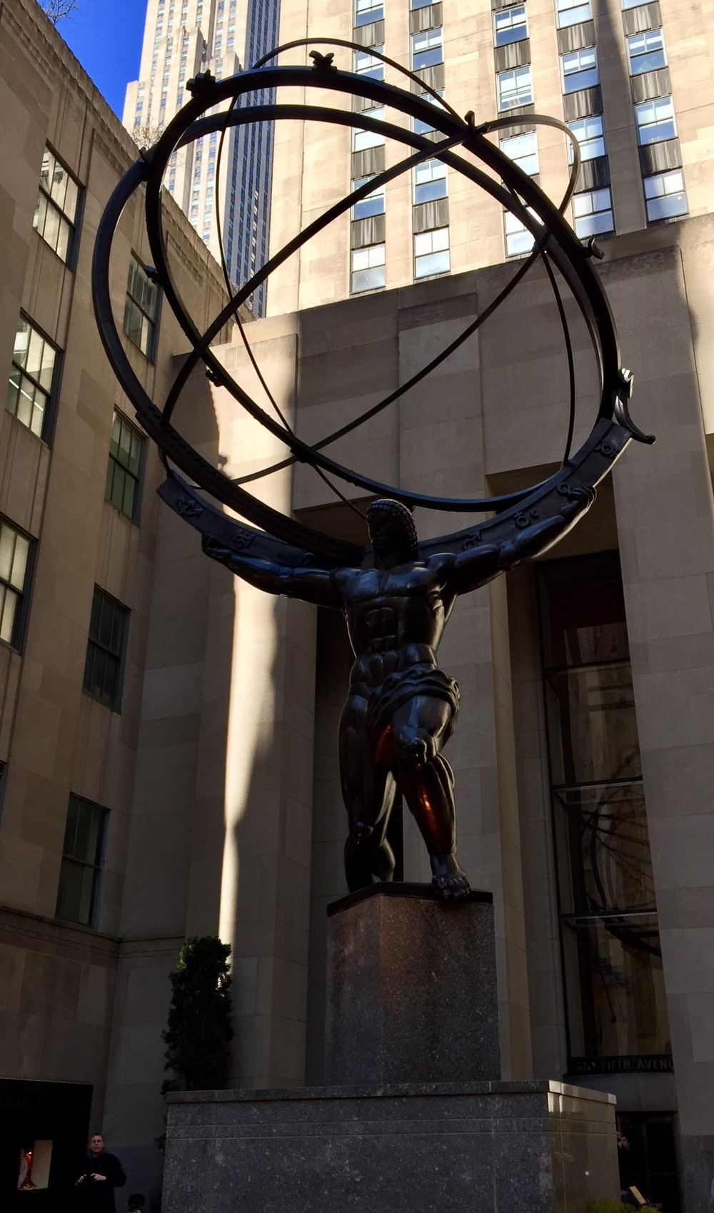 man holding globe statue near building at daytime