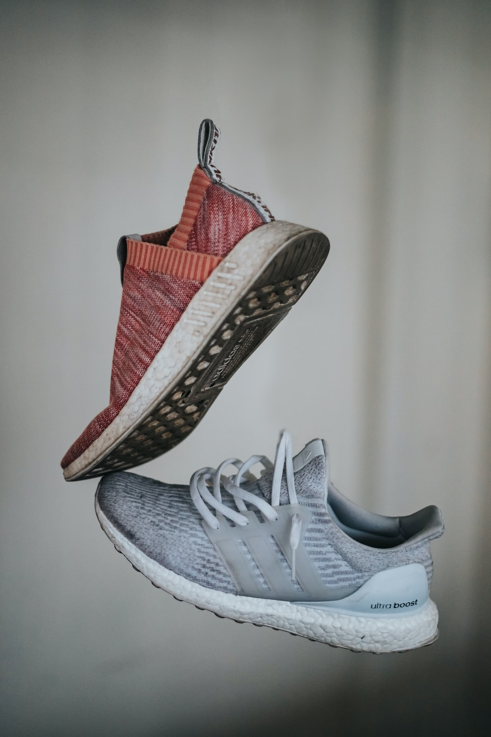 two unpaired brown and gray adidas running sneakers
