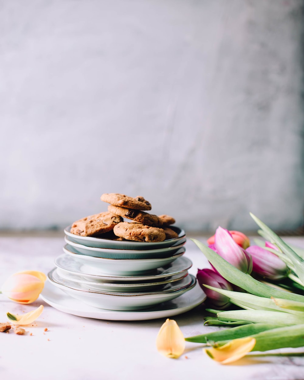 cookies on round white ceramic saucers beside pink tulips flowers