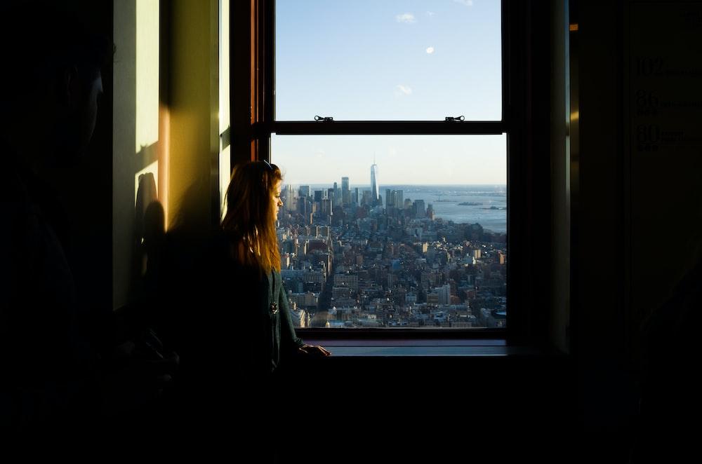 woman standing near window inside room