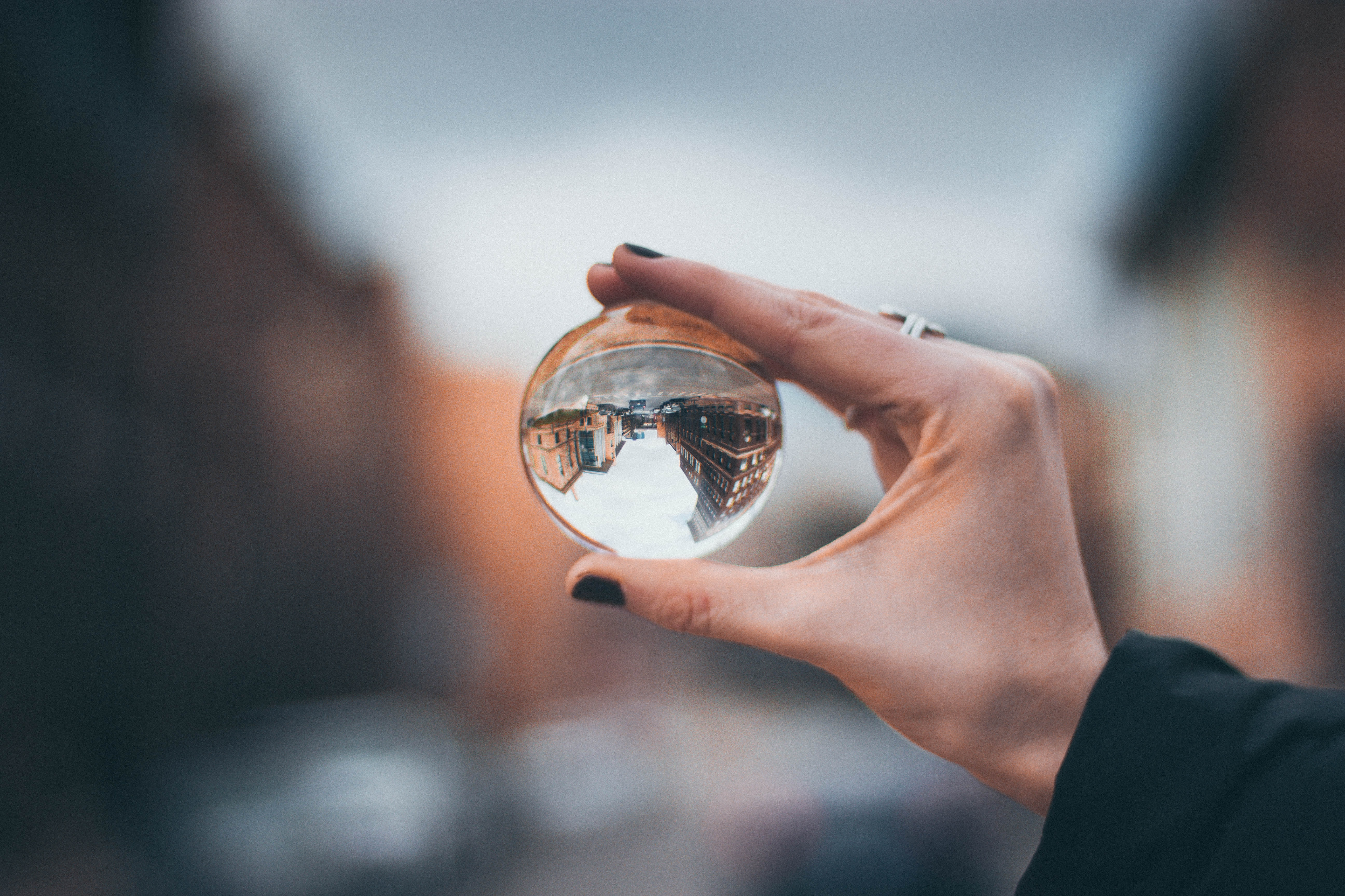 selective focus photography of woman holding clear glass ball