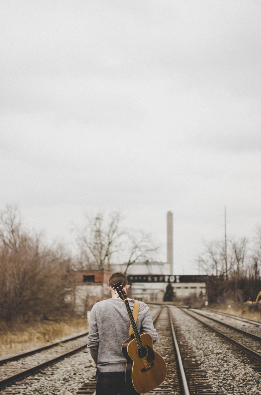 man carrying guitar walking on train rails