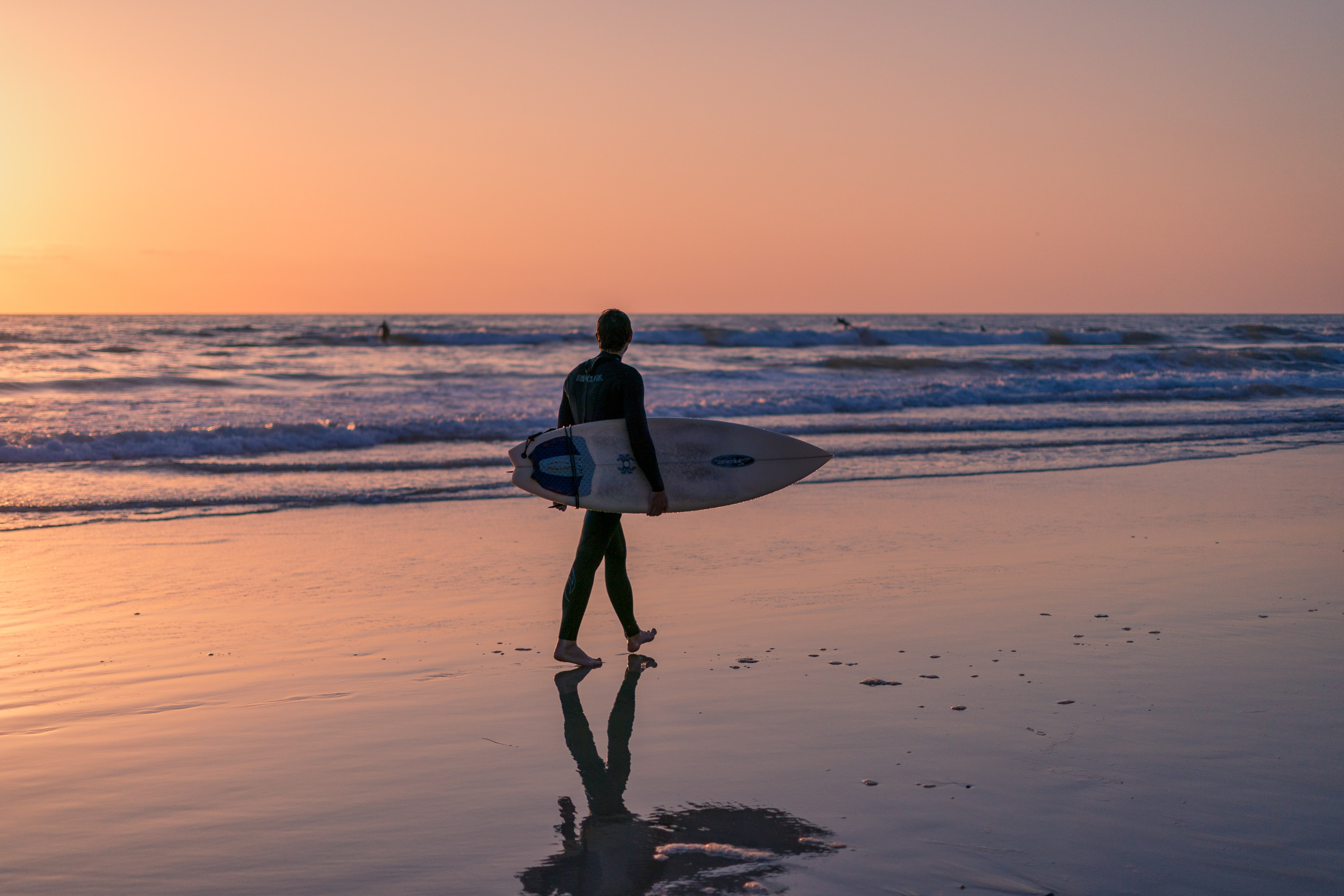 photo of man holding surfboard on seashore