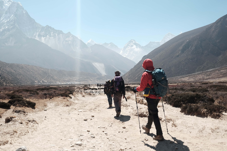 people hiking towards mountain ranges