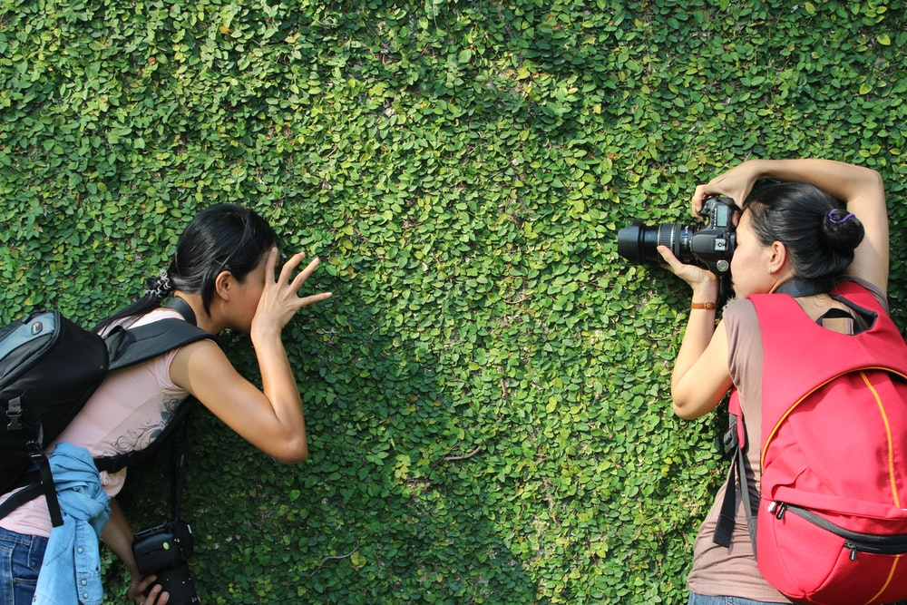 woman taking a picture of woman leaning in a green grass wall