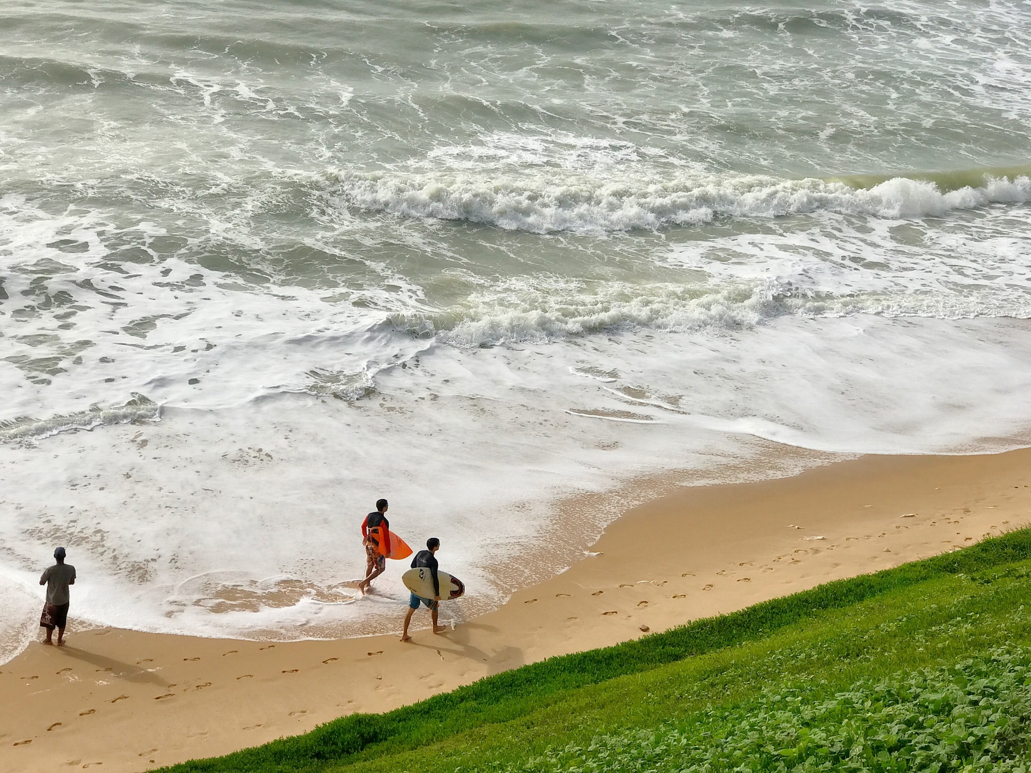 two person holding surfing board while walking on seashore at daytime