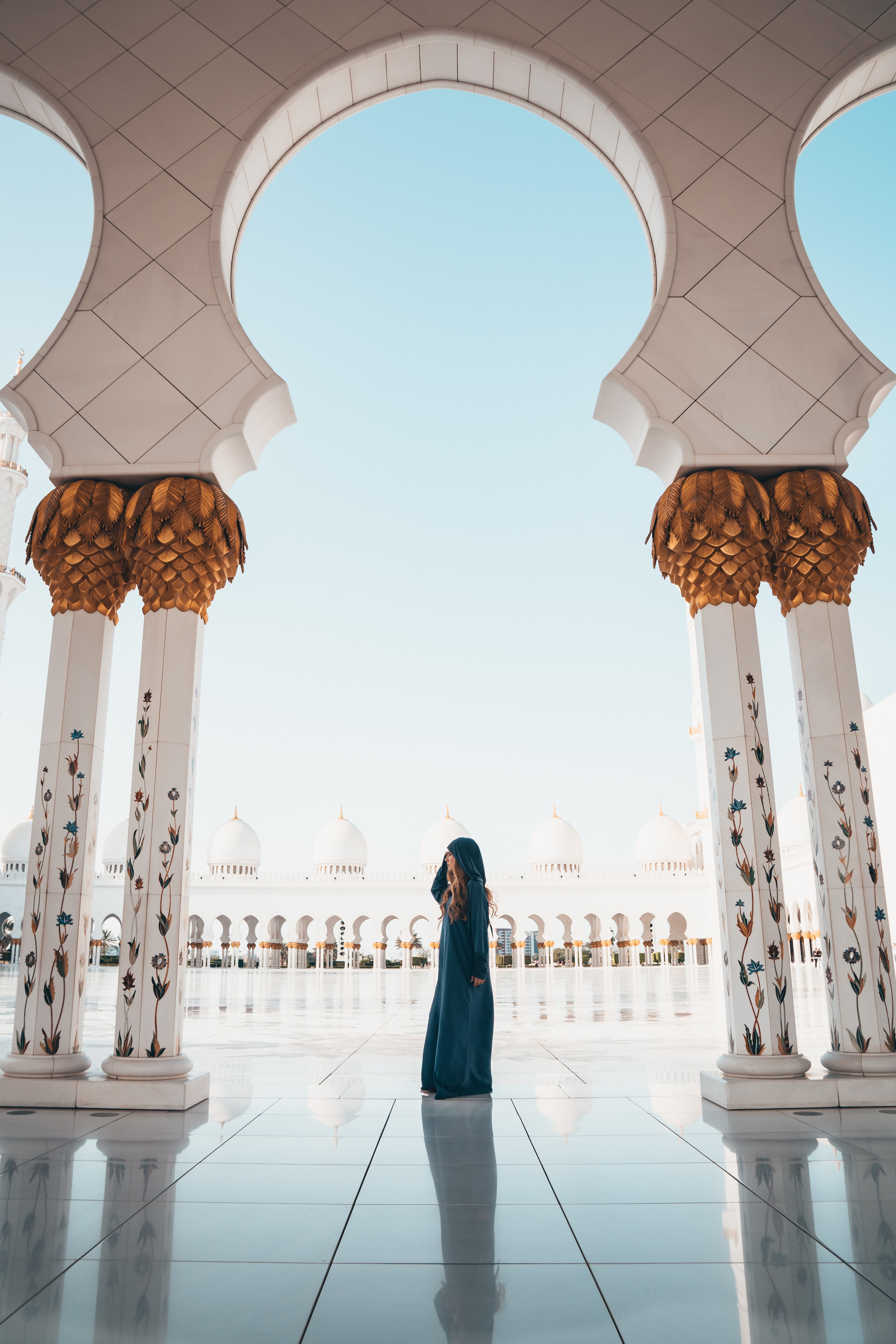 woman standing on white tiled floor in the middle of concrete pillars