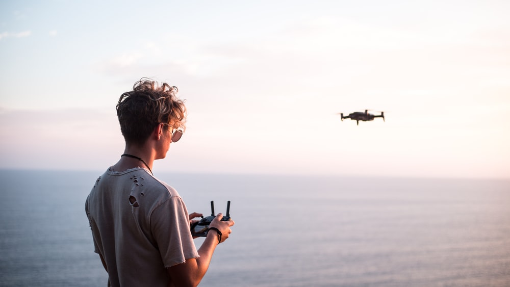 man using quadcopter drone near sea during daytime