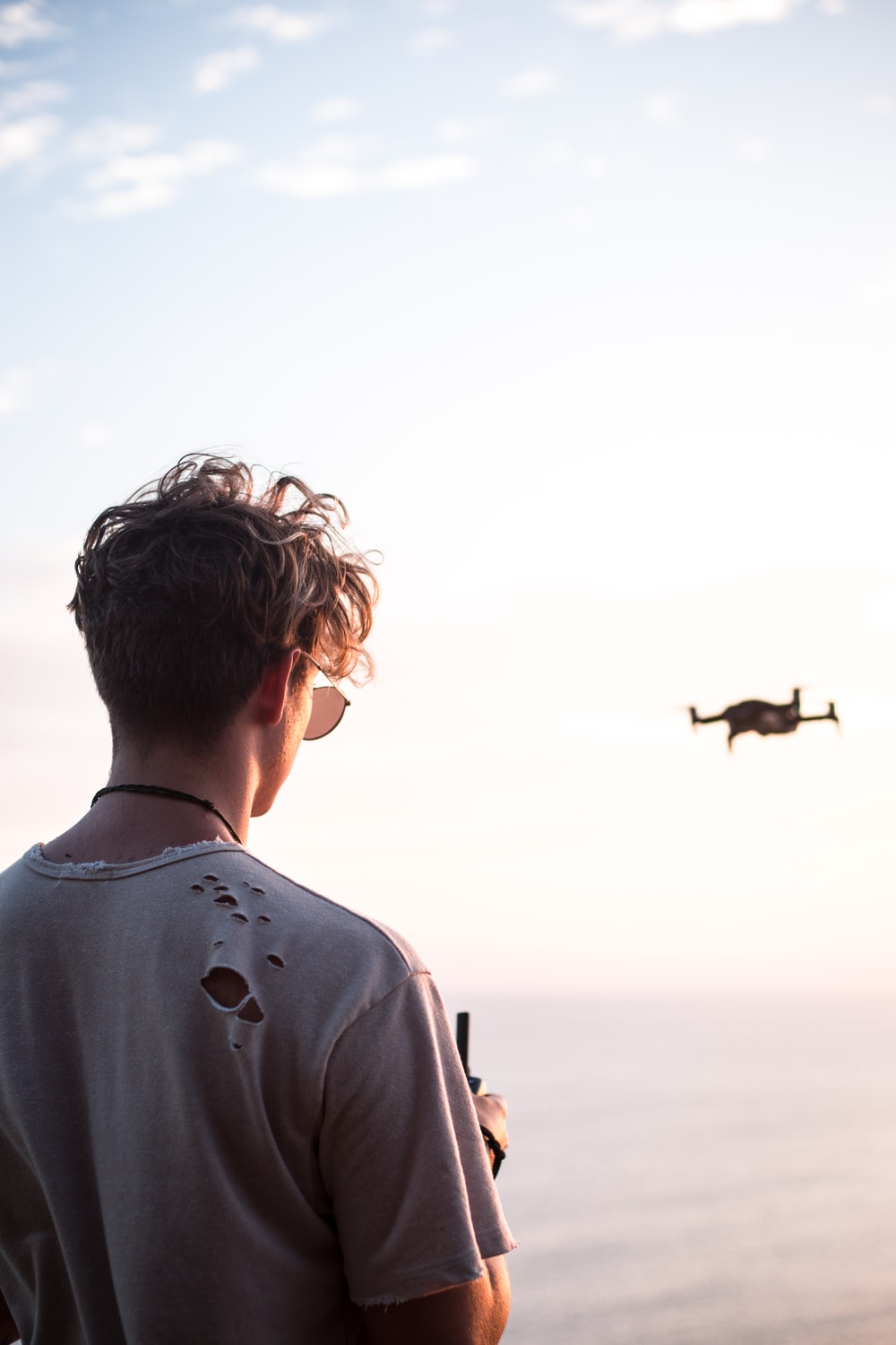 man controlling drone at daytime