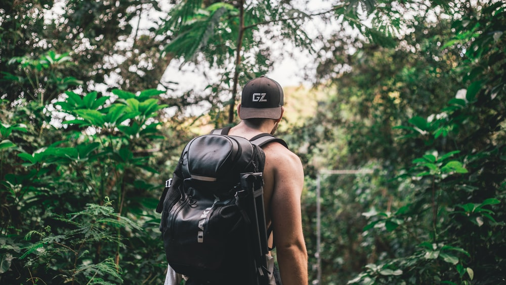 man carrying backpack in front of trees during daytime