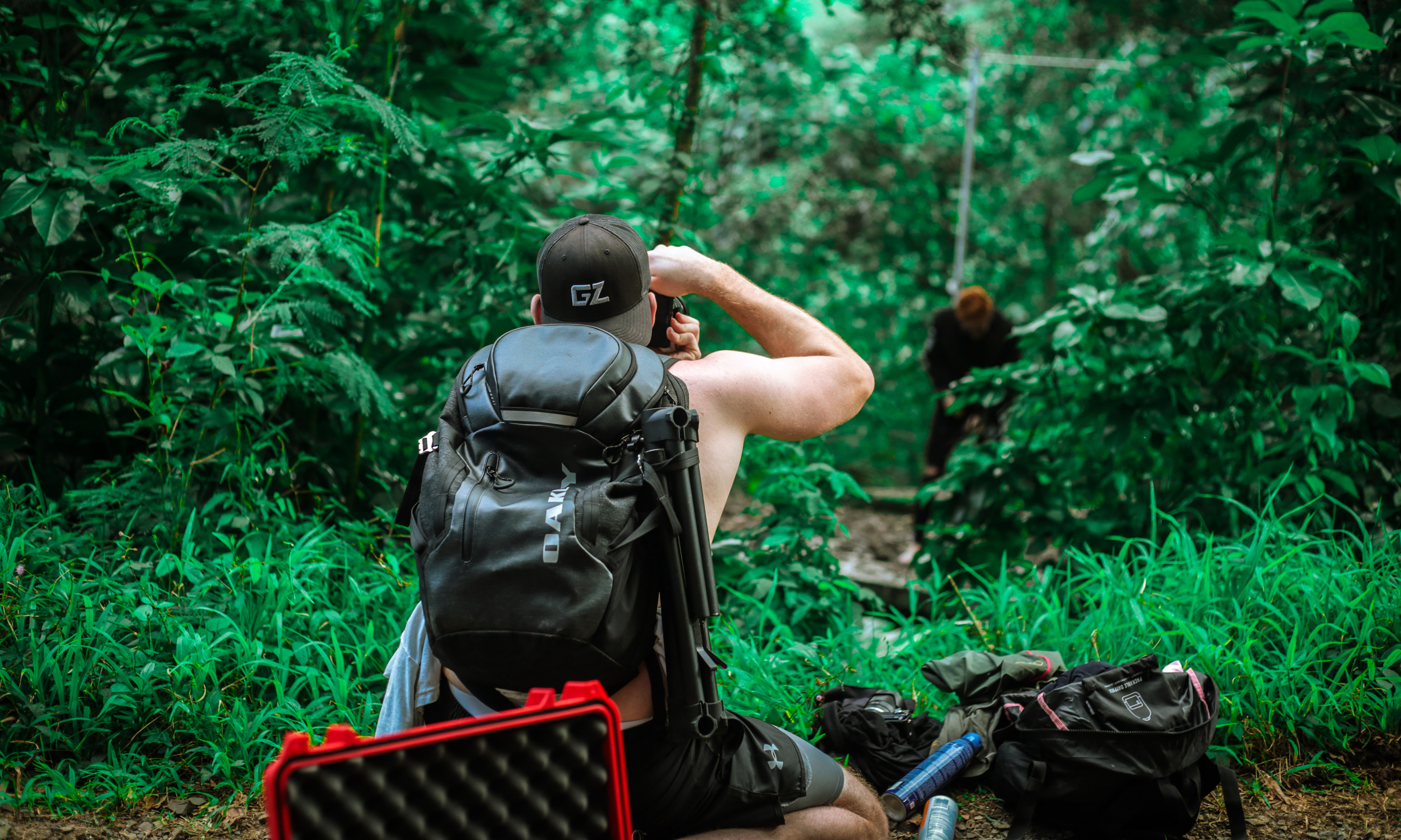 man carrying backpack taking photo of man standing beside trees