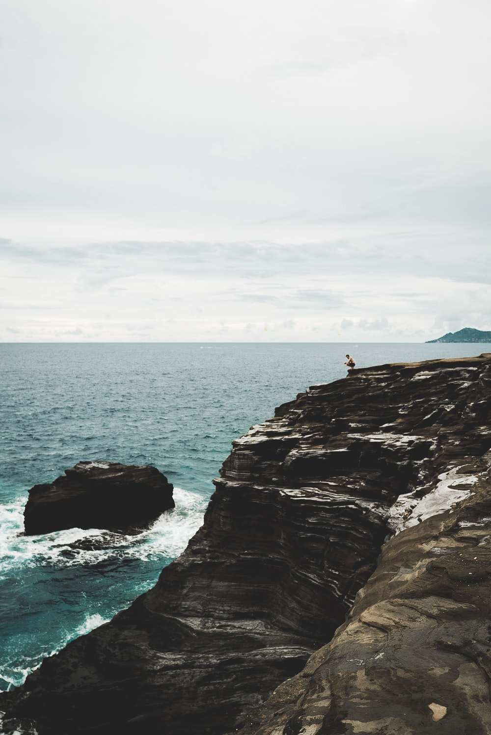 person sitting on cliff near body of water