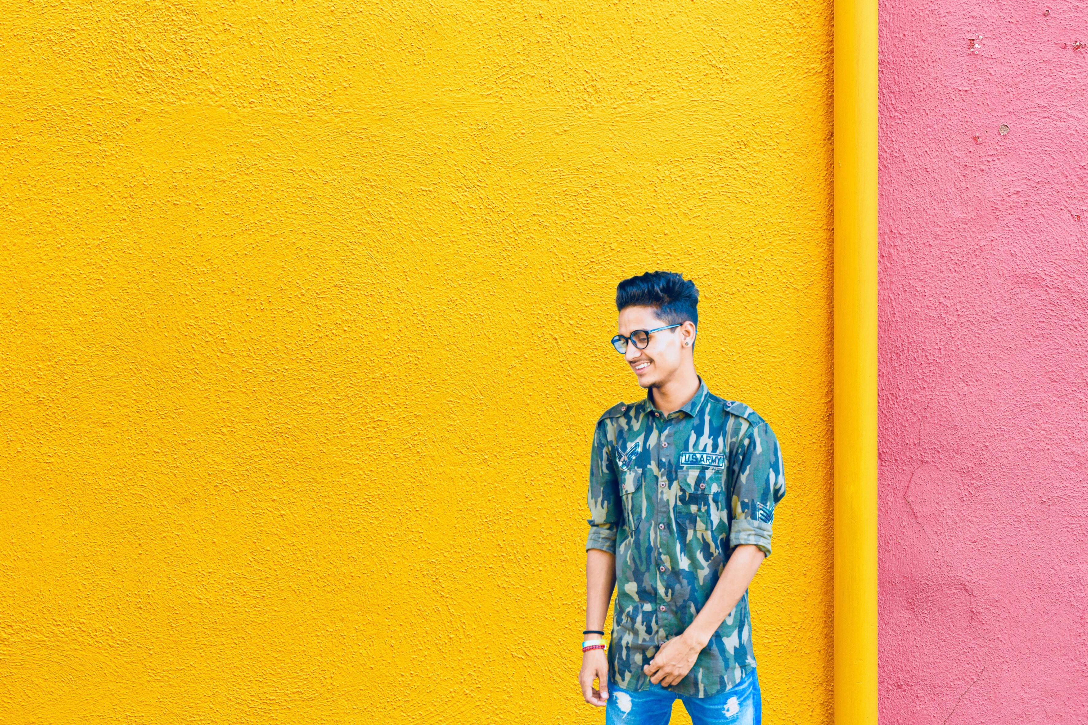 smiling man standing near yellow and pink wall