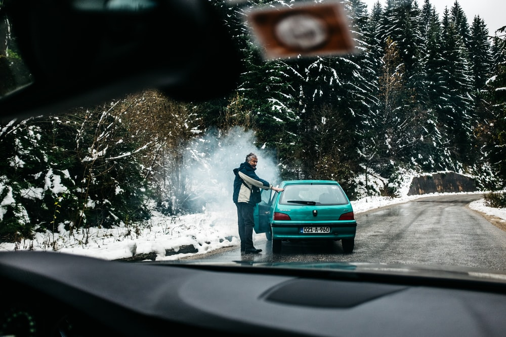 man standing in front of teal vehicle hatchback