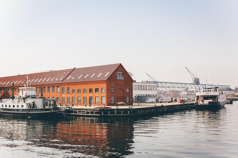white yacht beside orange house