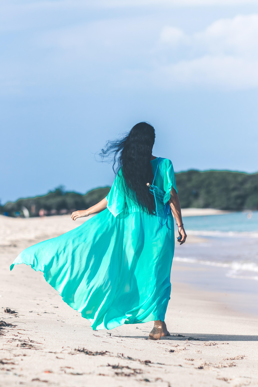 woman in blue short-sleeved dress waling beside body of water