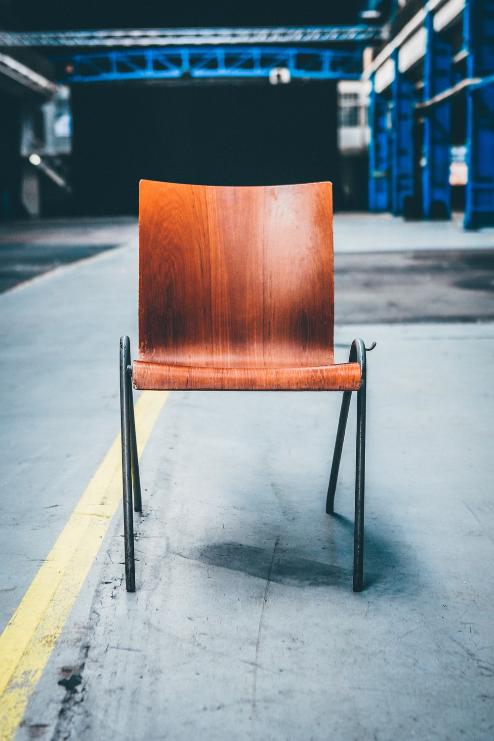 brown wooden chair with black metal base on gray pavement