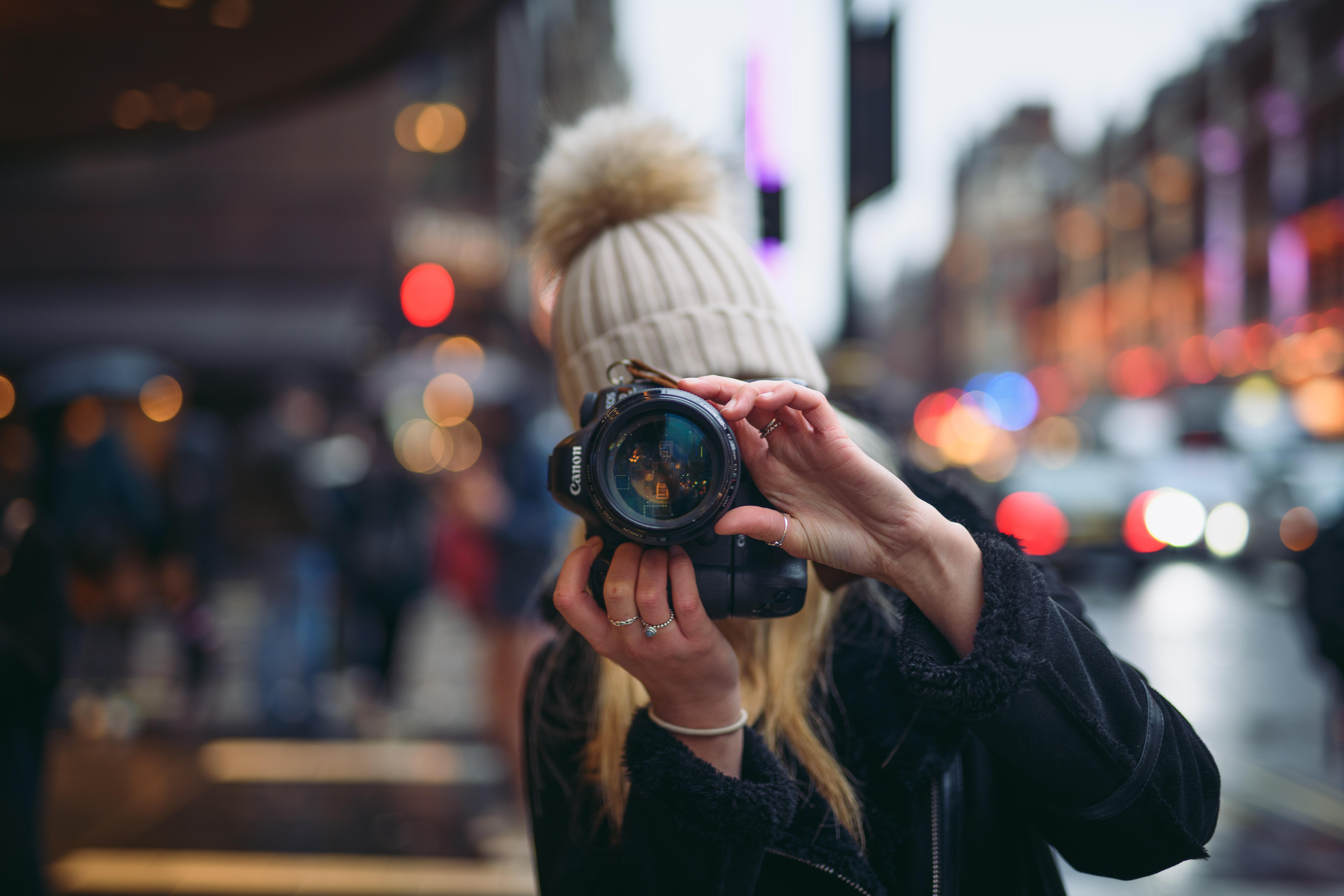 woman holding Canon DSLR camera