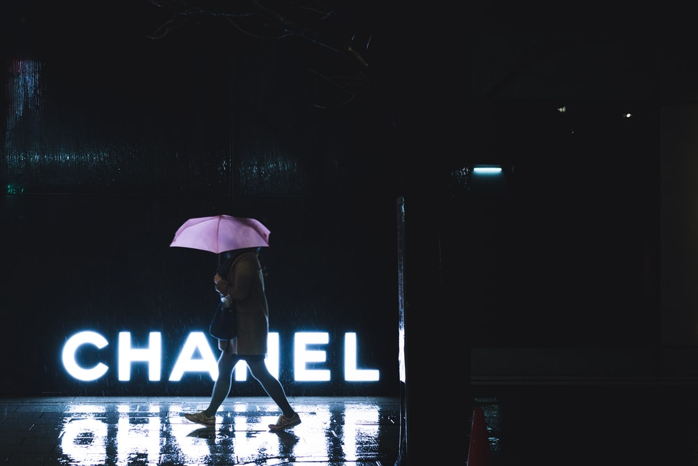woman walking under umbrella passing by Chanel lighted signage