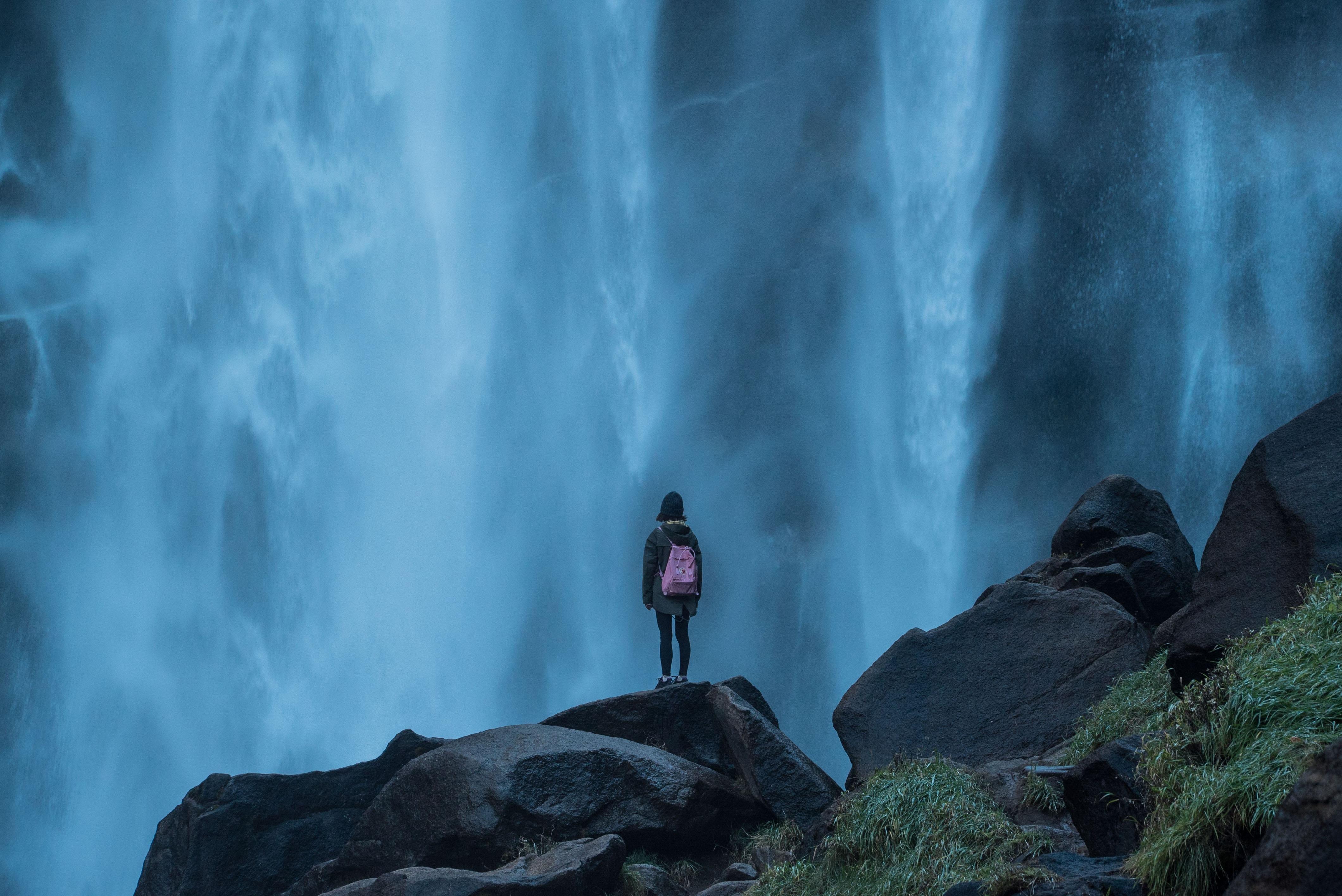 woman standing on edge waterfalls