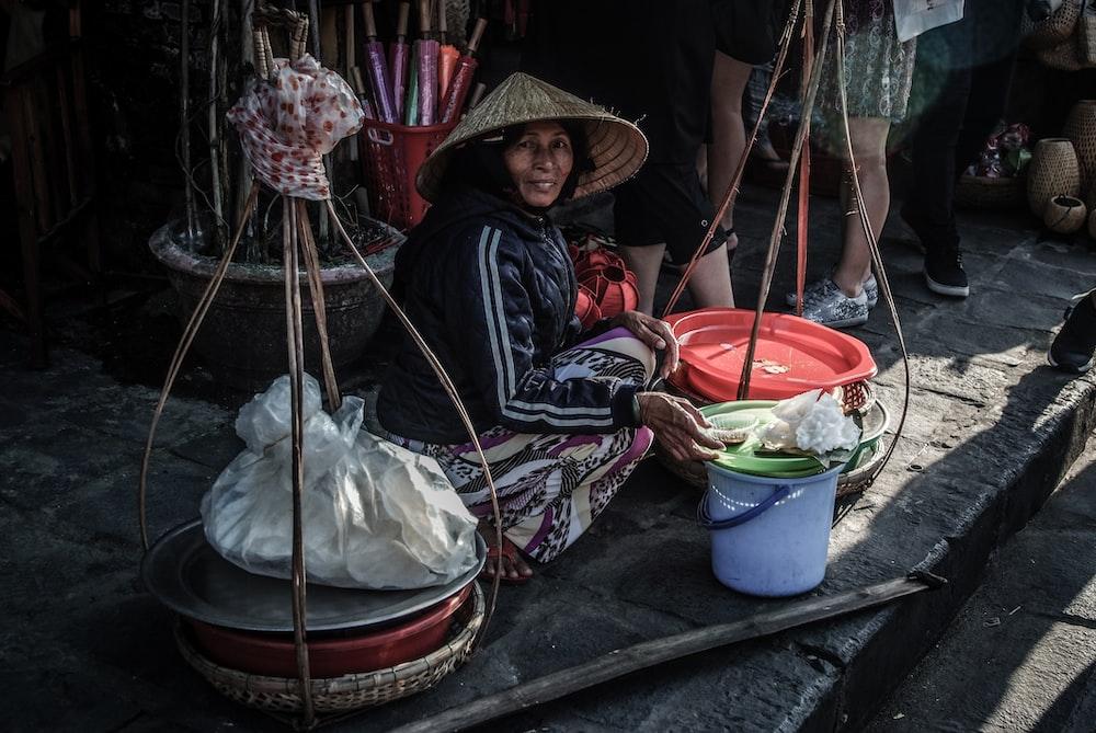 woman sitting beside street bucket
