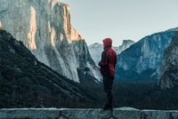 person wearing red hooded jacket standing on rock facing of yosemite park