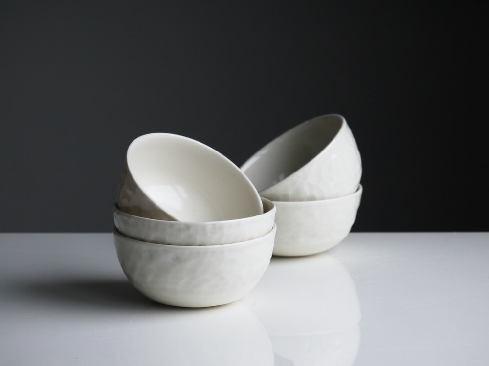 five round white ceramic bowls on white surface