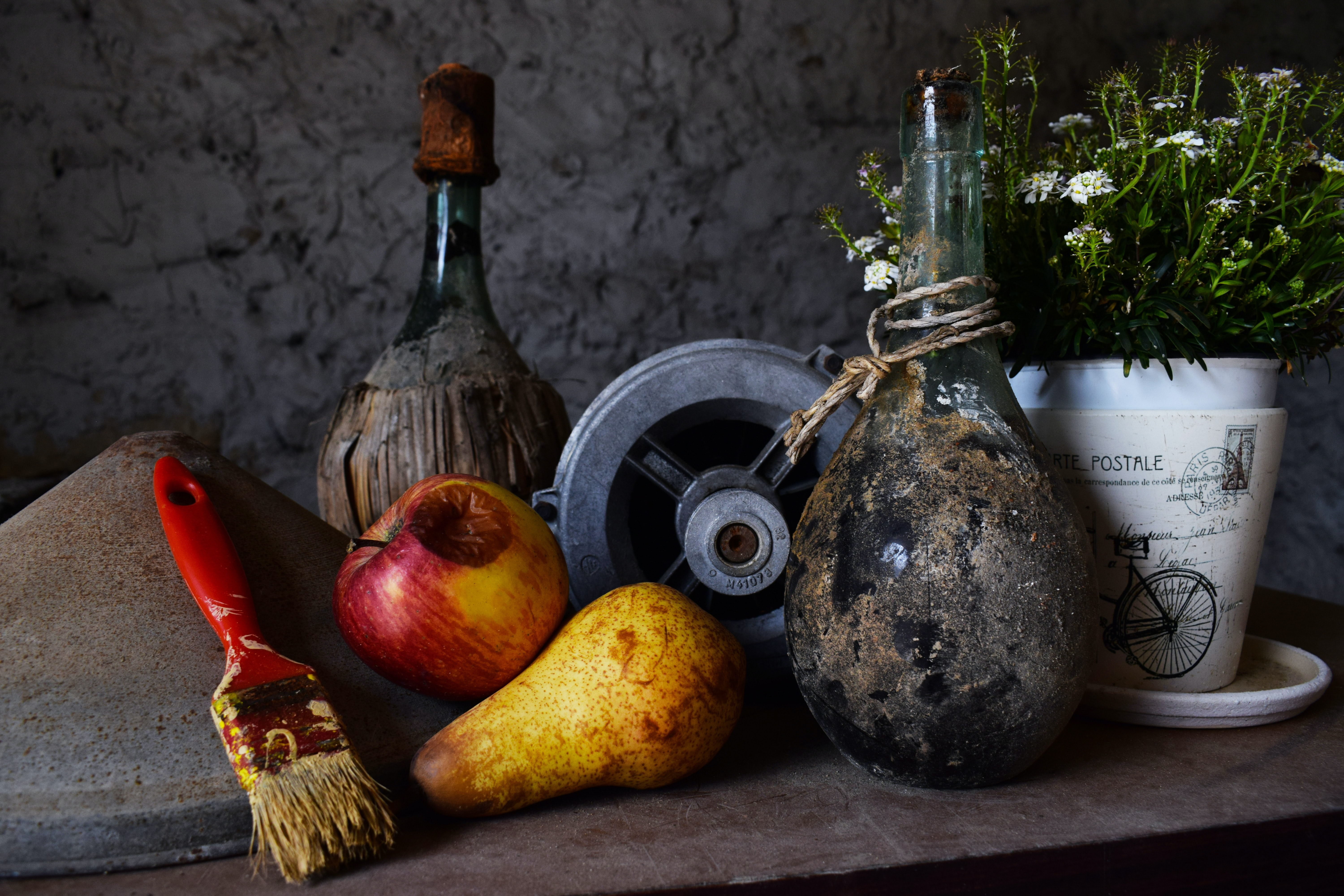 vase beside flower pot and fruits on table