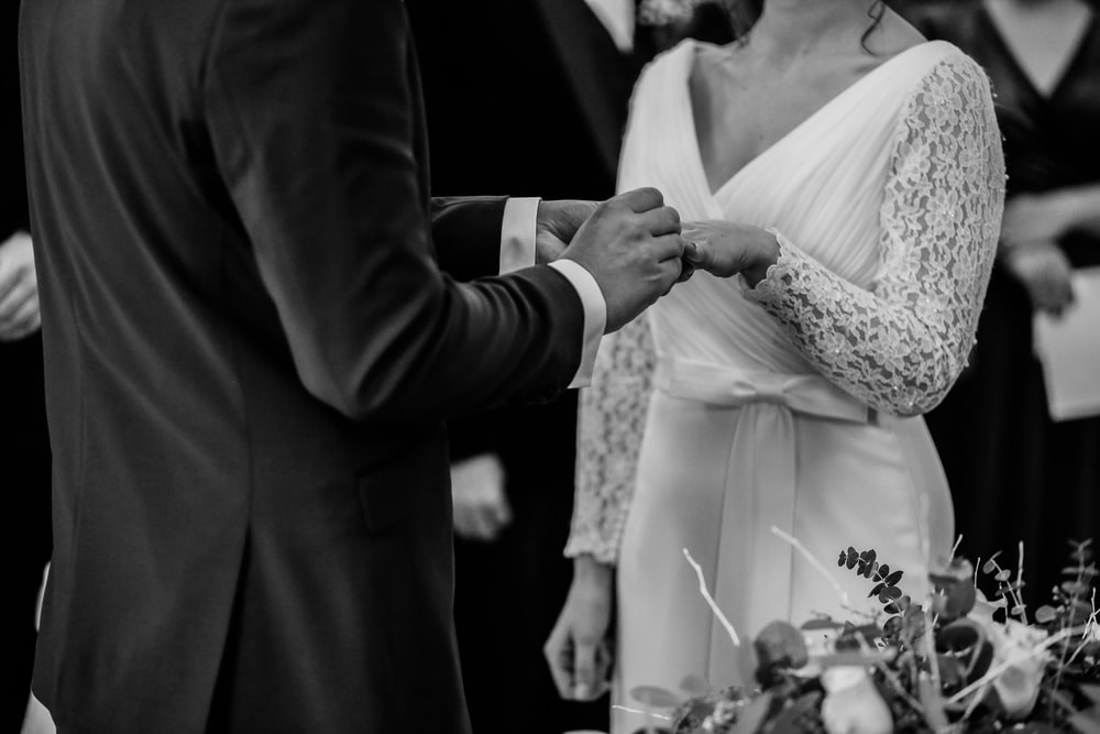 grayscale photo of man insert ring into woman during wedding ceremony
