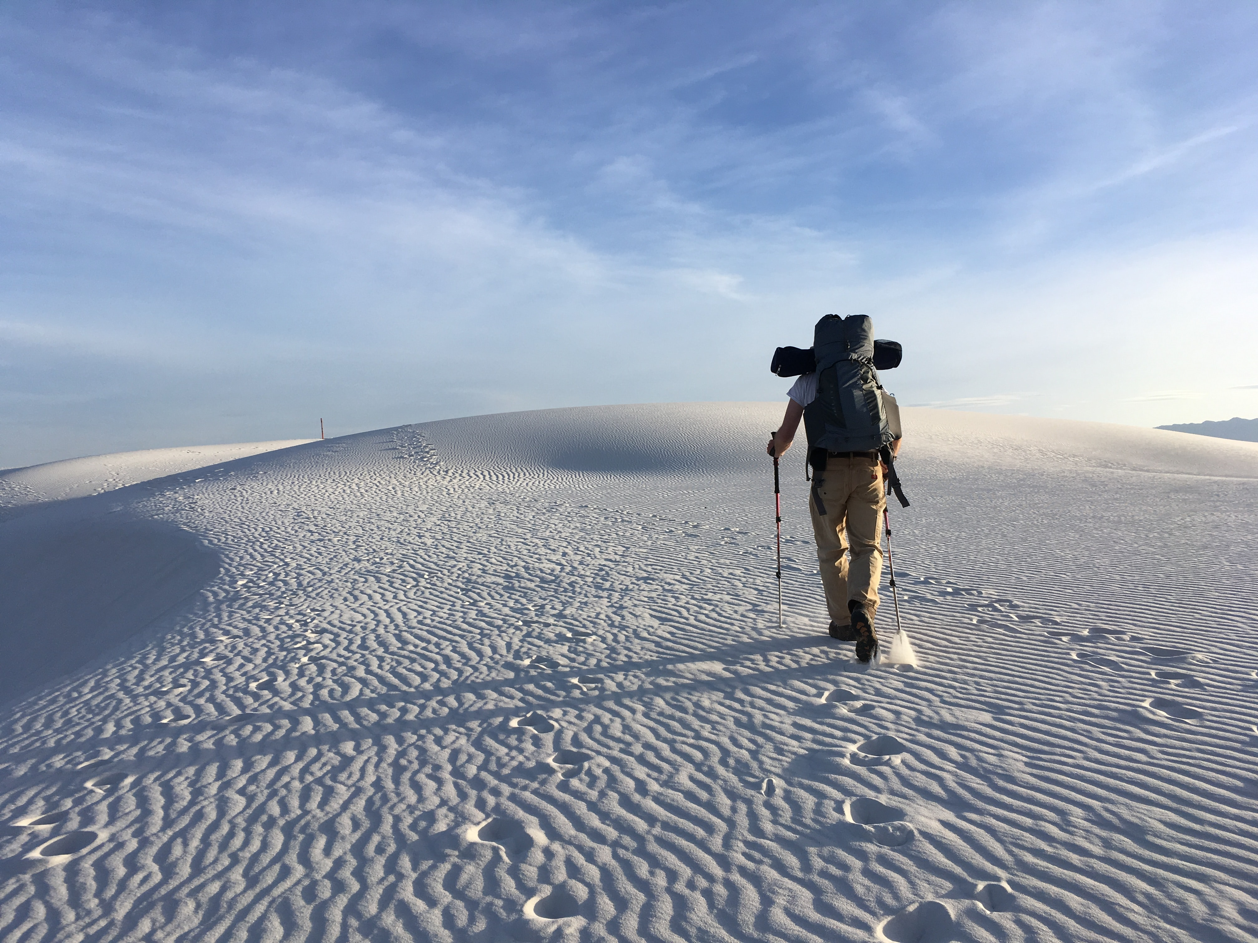 person hiking on sand dunes under white skies during daytime