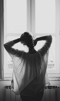 grayscale photograph of woman standing in front of window