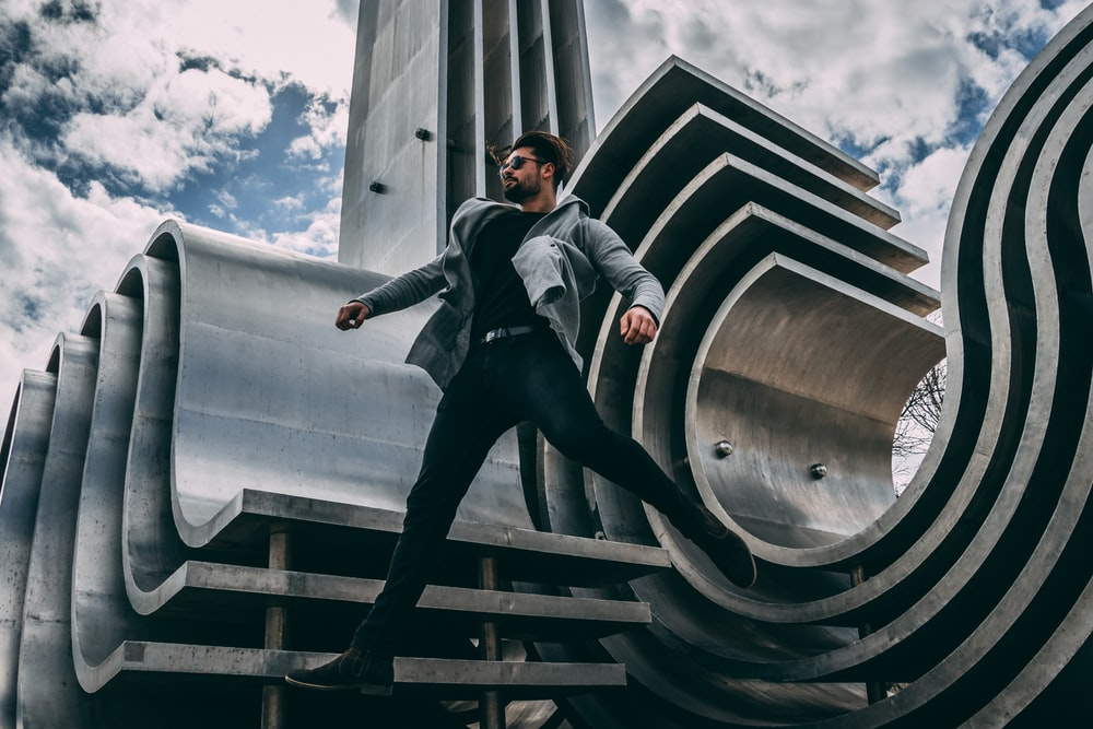 man jumping beside gray architecture